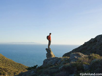Hispanic man standing on rock overlooking water. Picture of a young hiker standing on a rock outcropping on the edge of a cliff overlooking the ocean. The young man is wearing an orange shirt and has a backpack on his back.